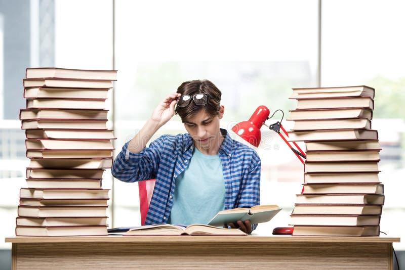 Студент молодого человека подготавливая для экзаменов коллежа стоковое фото