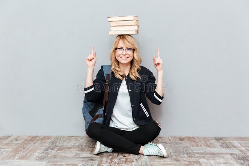 Студент молодой женщины держа книги на голове и указывать стоковая фотография