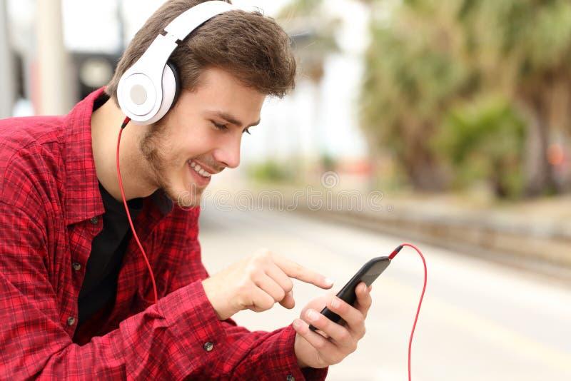 Студент подростка уча с онлайн курсом в умном телефоне