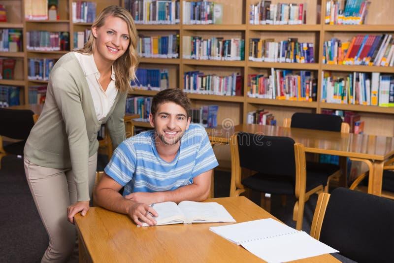 Студент получая помощь от гувернера в библиотеке стоковые изображения