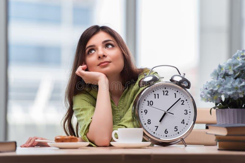 Студент при будильник gian подготавливая для экзаменов стоковое фото