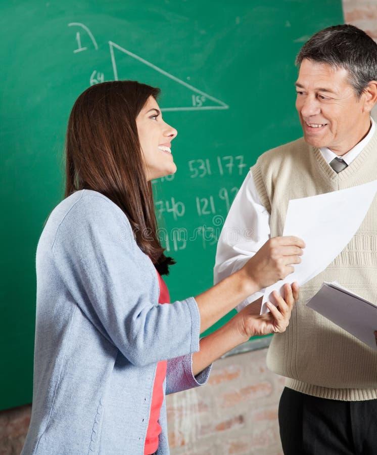 Студент при результат экзамена смотря учителя внутри стоковые фото