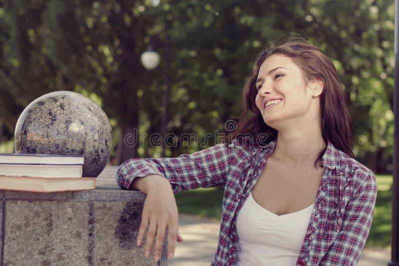 Студент стоя в парке и смеясь над весело стоковые фото