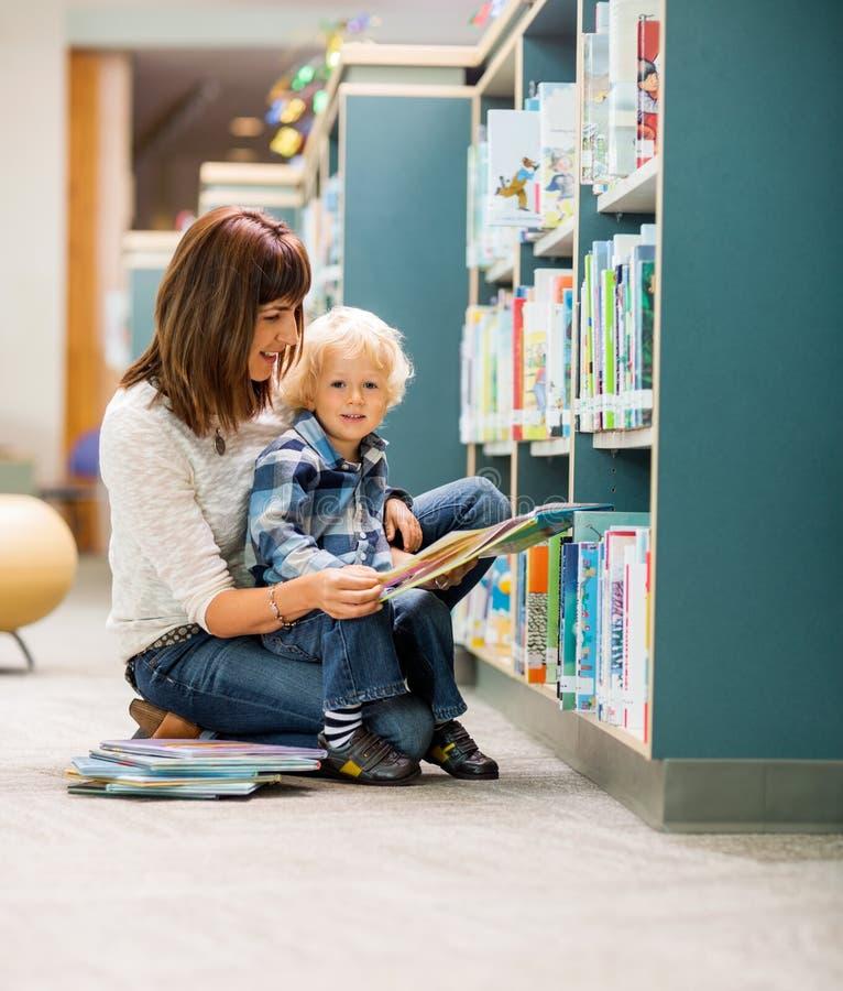 Студент с книгой чтения учителя в библиотеке стоковые фотографии rf