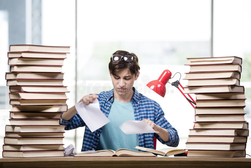 Студент с сериями книг подготавливая для экзаменов стоковые изображения rf