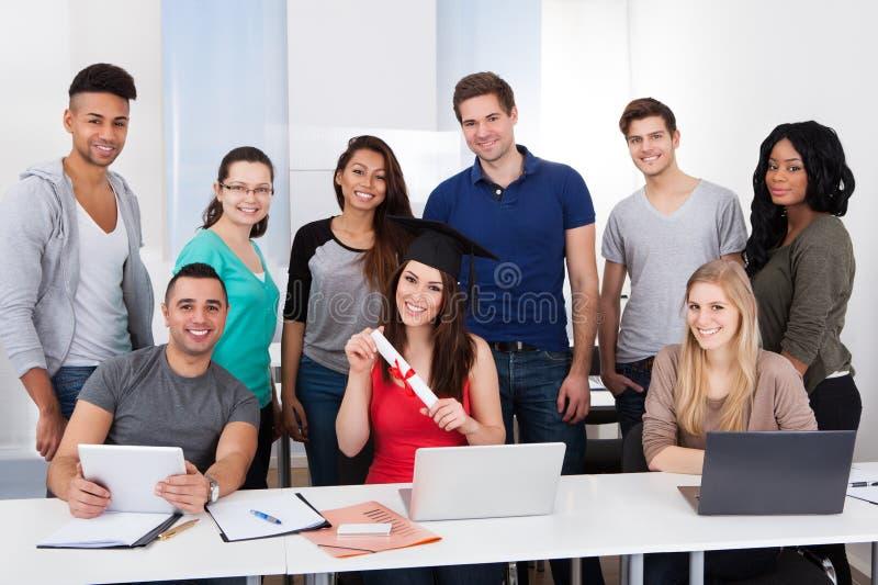 Студент университета держа степень в классе стоковое изображение rf