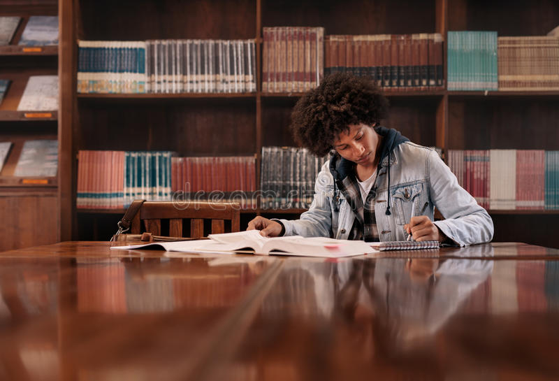 Студент университета делая назначение в библиотеке стоковое фото rf