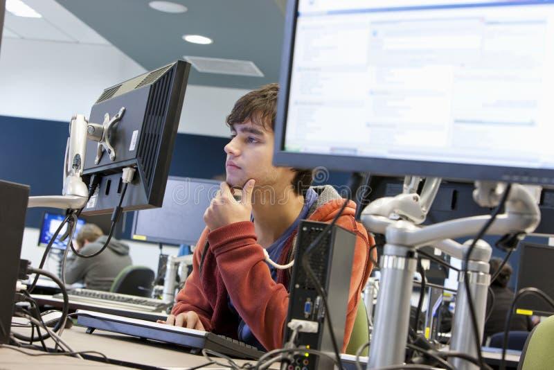 Студент университета используя компьютер стоковое фото rf