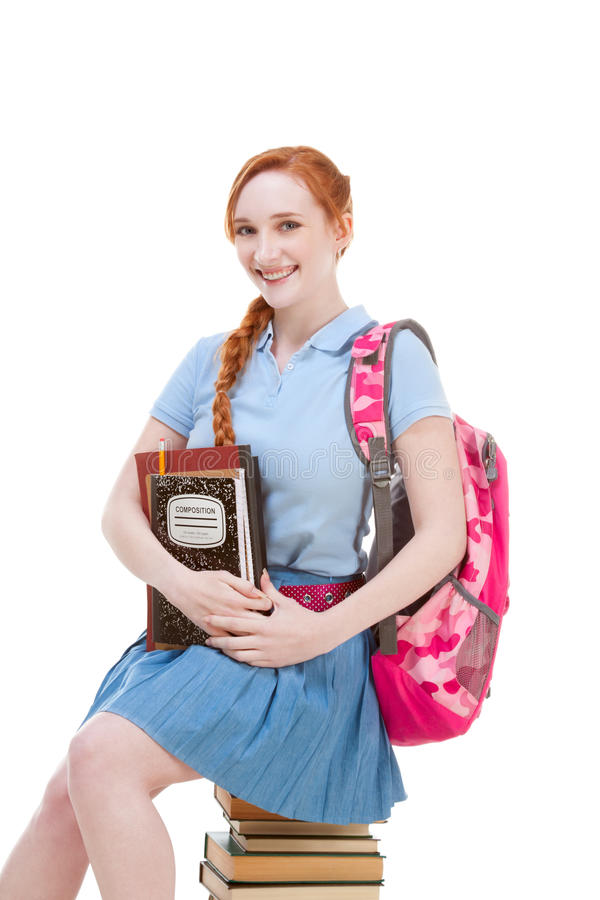 Студент школьницы средней школы сидя на стоге книг стоковое изображение rf