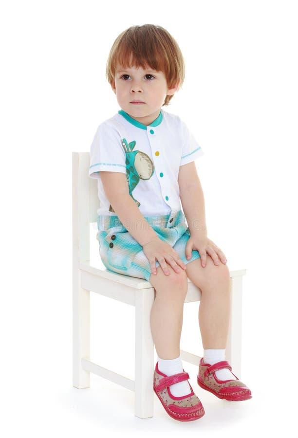 стул мальчика немногая сидя стоковая фотография