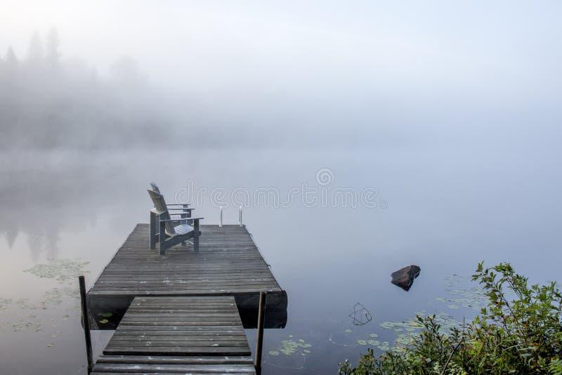 Стулья на доке обозревая озеро в тумане раннего утра - стоковые изображения rf