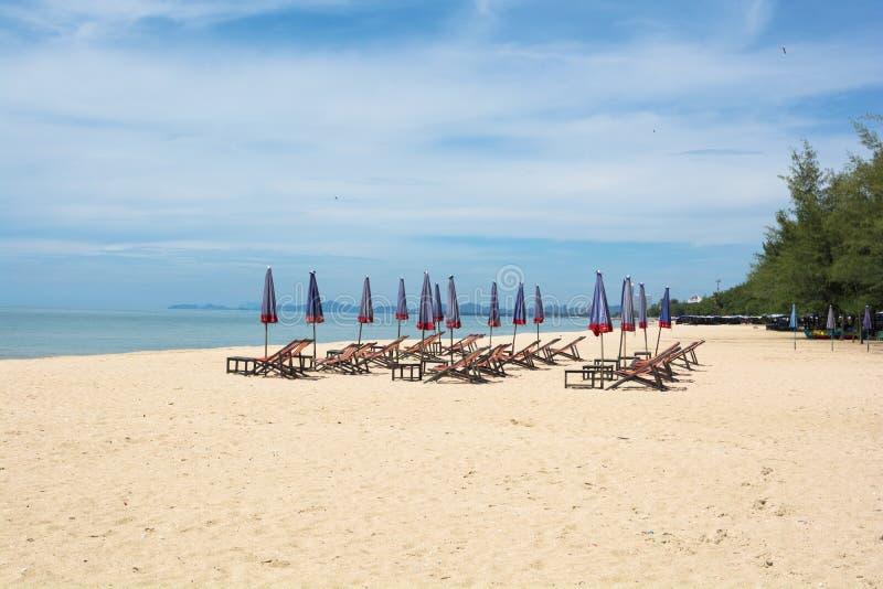 Стулья на песчаном пляже около моря стоковое изображение