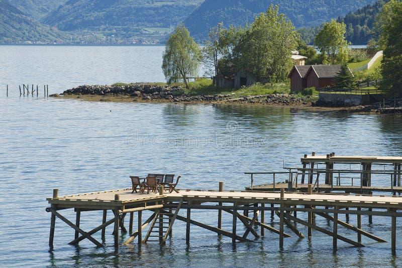 Стулья на пристани фьорда в Balestrand, Норвегии стоковые фотографии rf
