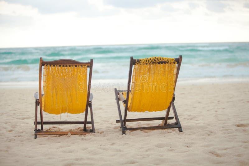 Стулья пляжа желтые на каникулы на тропическом стоковое изображение