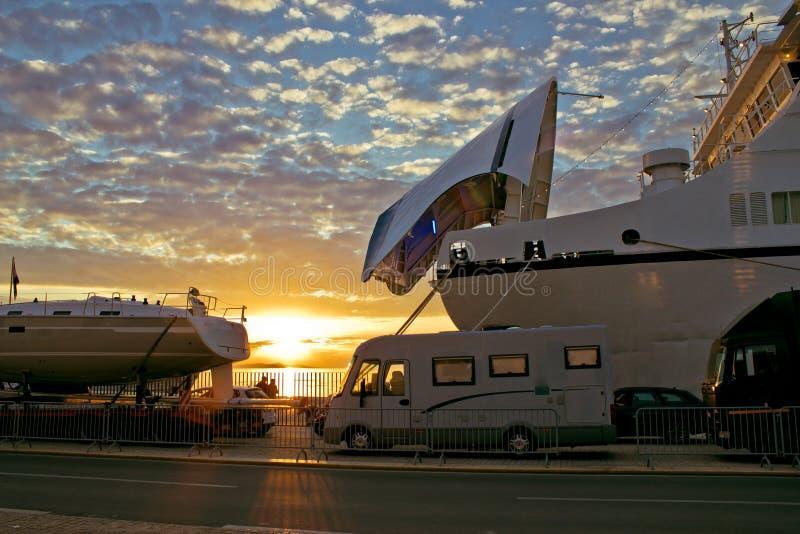 стыковки шлюпки ferry заход солнца стоковые изображения rf