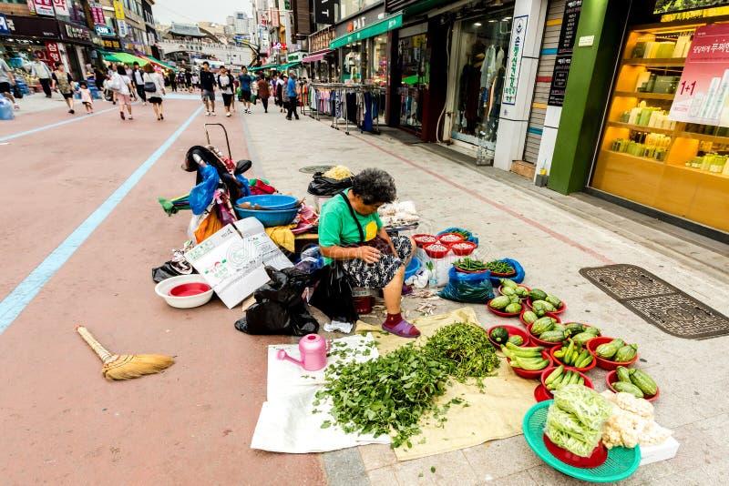 Сувон, Южная Корея - 25-ое июня 2017: Женщина поставщика продавая овощи и плоды в уличном рынке в центре города в Сувоне стоковые фотографии rf