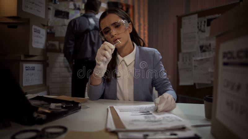 Судебнохимическая дама ученого рассматривая пулю доказательства от места преступления стоковая фотография rf