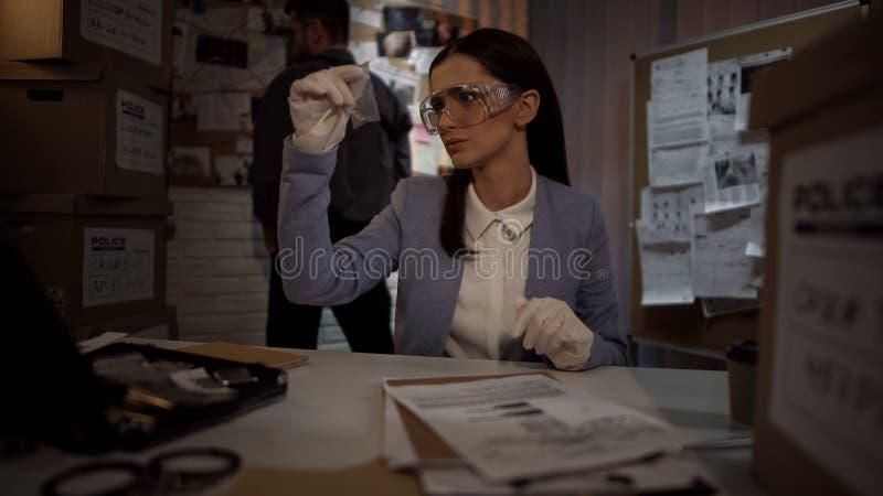 Судебнохимическая женщина ученого в перчатках рассматривая пулю доказательства, находя ключ стоковое фото