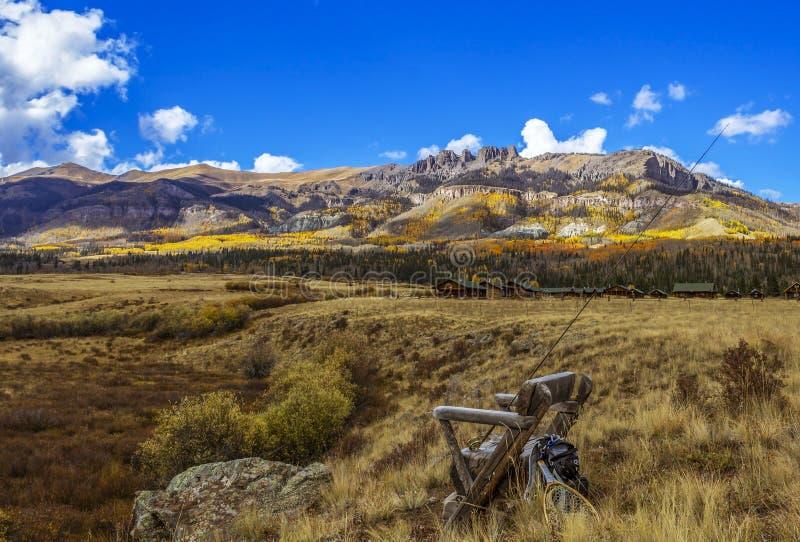 Суд с рыболовными принадлежностями мухы с фоном скалистой горы Колорадо стоковые фото