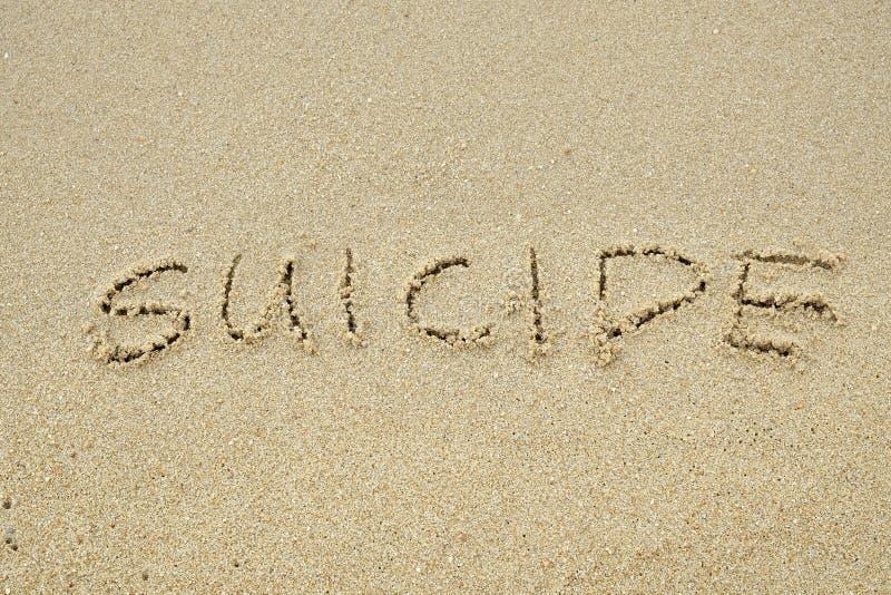 СУИЦИД написанный на песке стоковая фотография rf