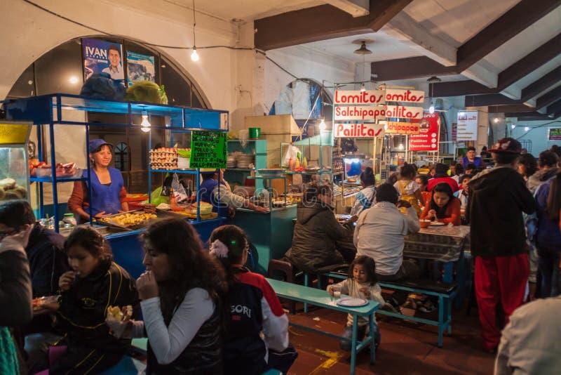 СУКРЕ, БОЛИВИЯ - 21-ОЕ АПРЕЛЯ 2015: Местные люди сидят на закусочных на рынке в Сукре, Boliv стоковая фотография