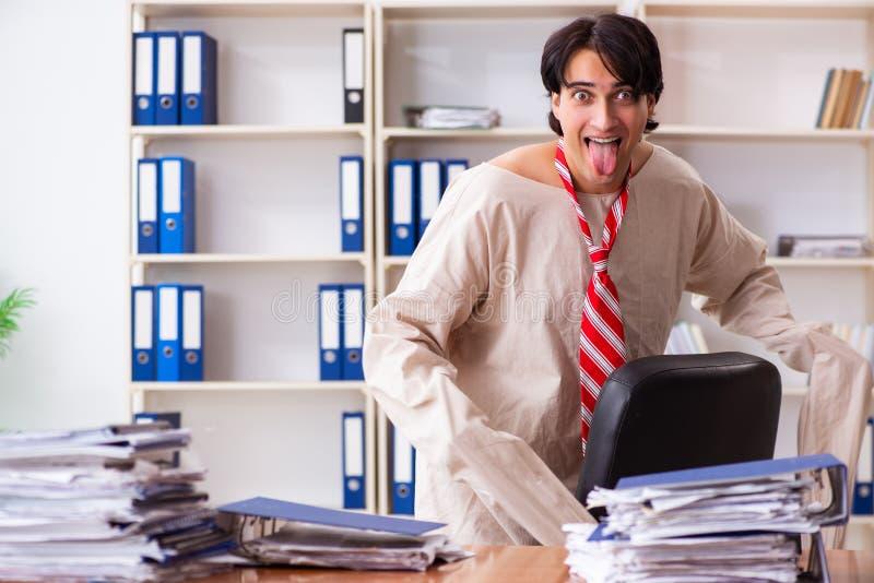 Сумасшедший молодой человек в смирительной рубашке на офисе стоковая фотография