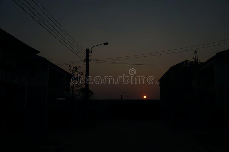 Сумерк Заход солнца до неба не будет красн с тенью деревни стоковое изображение rf