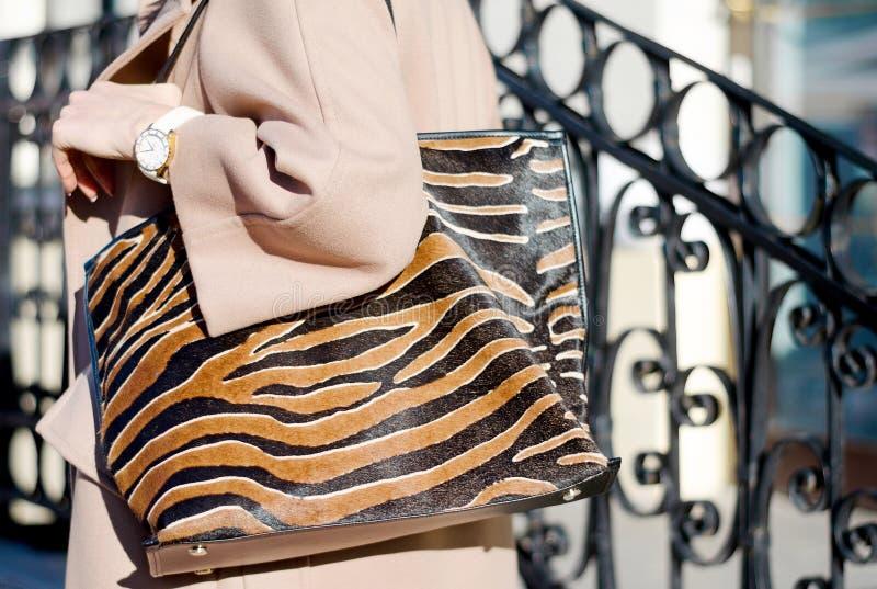 Сумка в конце-вверх печати леопарда большая ходя по магазинам кожаная сумка в женских руках Женщина идя в город Девушка в бежевом стоковое изображение