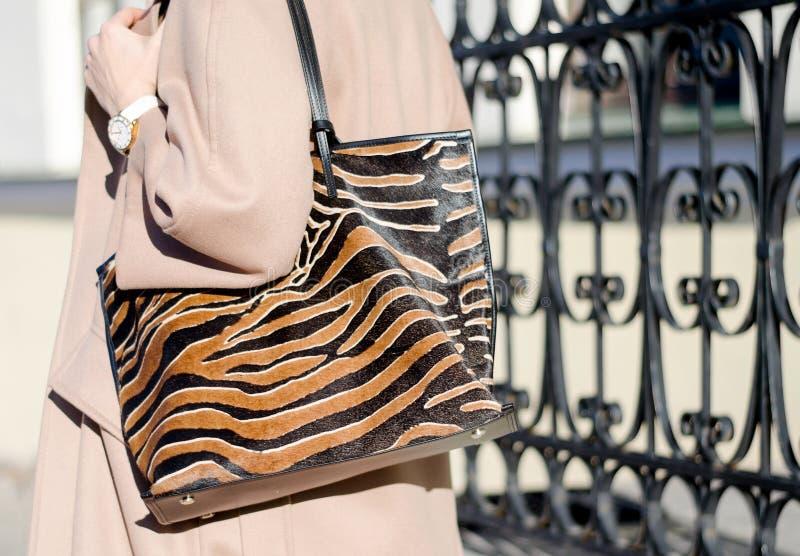 Сумка в конце-вверх печати леопарда большая ходя по магазинам кожаная сумка в женских руках Женщина идя в город Девушка в бежевом стоковые фотографии rf