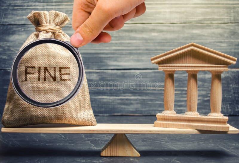 Сумка денег со штрафом слова и зданием суда или банком на весах правосудия Концепция оплачивать штраф Финансовый стоковое фото rf
