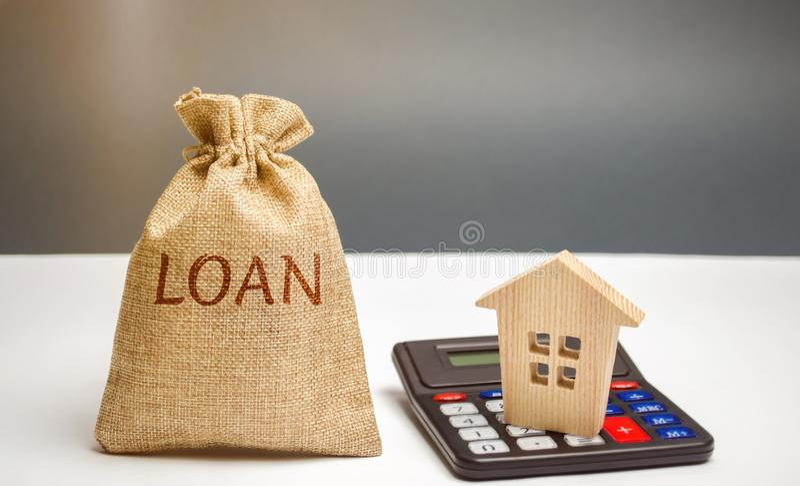 Сумка денег с займом слова и дом на калькуляторе Высчитывать займа Вычисление процентных ставок Кредит недвижимости ем стоковое фото rf