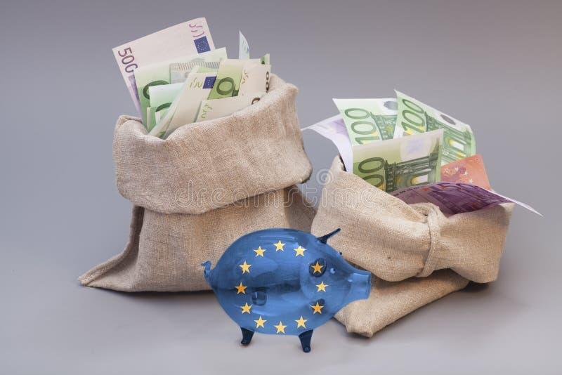 Сумка 2 денег с копилкой евро и стекла с флагом Европейского союза стоковая фотография