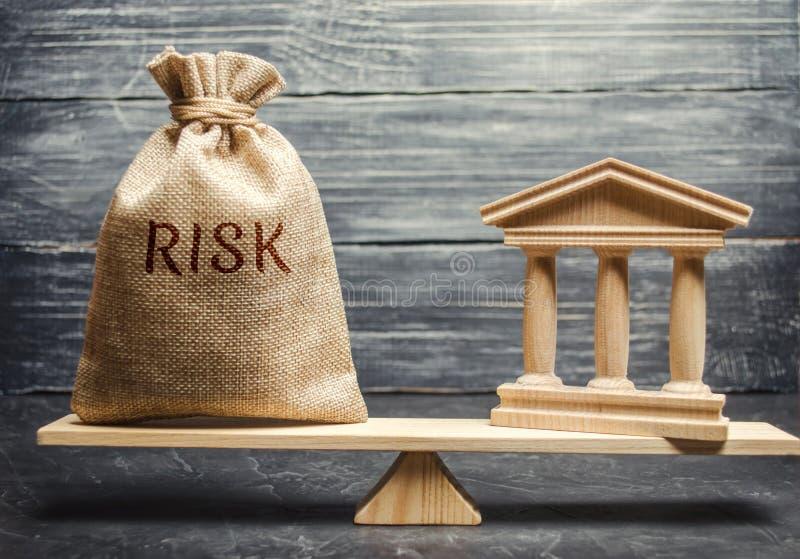 Сумка денег с риском слова и здание банка в масштабах Концепция финансового и экономического риска ненадежно стоковые изображения rf