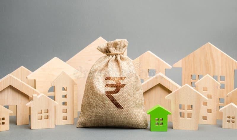 Сумка денег с рупией индийской рупии знака и деревянными домами Концепция рынка недвижимости Оценка и требование Бюджет города стоковые изображения rf