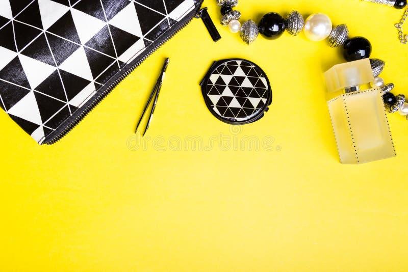 Сумка женщины с составом и аксессуары на желтой предпосылке Плоское положение стоковое фото rf