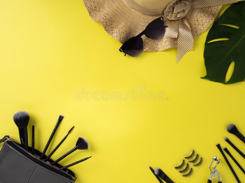 Сумка макияжа с разнообразием предпосылки продуктов красоты желтой стоковые фотографии rf