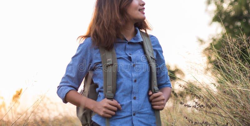 Сумка нося красивой женщины путешественников в заходах солнца поля стоковые фото