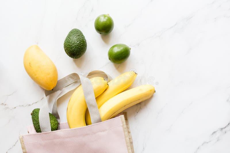 Сумка пинка взгляда сверху различной свежей здоровой еды лежа на белой мраморной предпосылке r r Минимальный многоразовый отход стоковое изображение