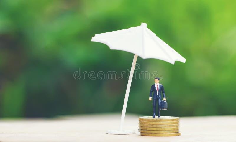 Сумка портфеля удерживания бизнесмена согласования продаж концепции страхования продаж и бизнесмен зонтика защищая на золотой мон стоковое фото