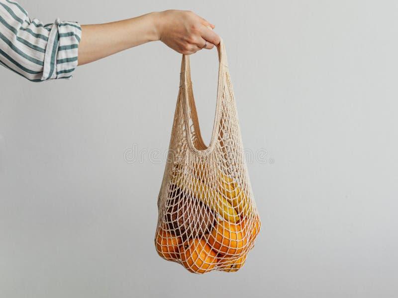 Сумка сетки владением руки женщины стоковое изображение