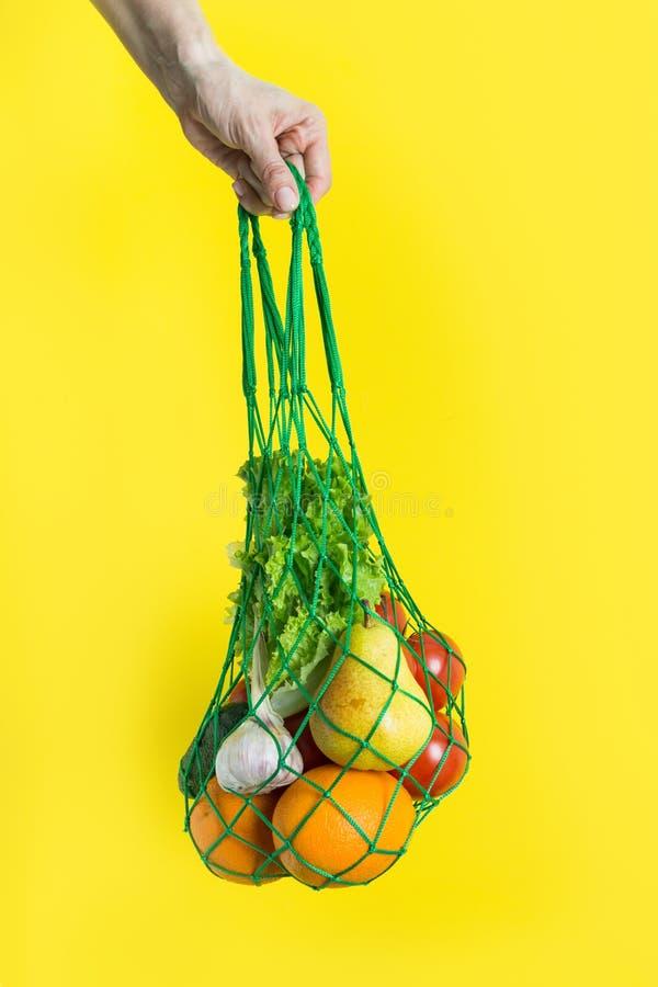 Сумка сетки плодов, овощей, зеленых цветов в руке женщины E Пластиковый освободите r стоковое изображение
