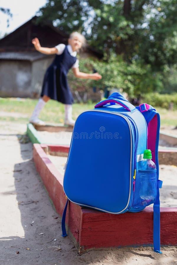 Сумка школы и элементарный студент на спортивной площадке стоковое изображение