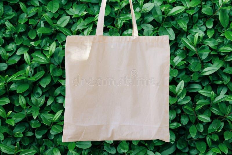 Сумка Tote хлопка модель-макета Linen на зеленой предпосылке листвы деревьев Буша Природа Eco дружелюбная Экологический рециркули стоковые изображения