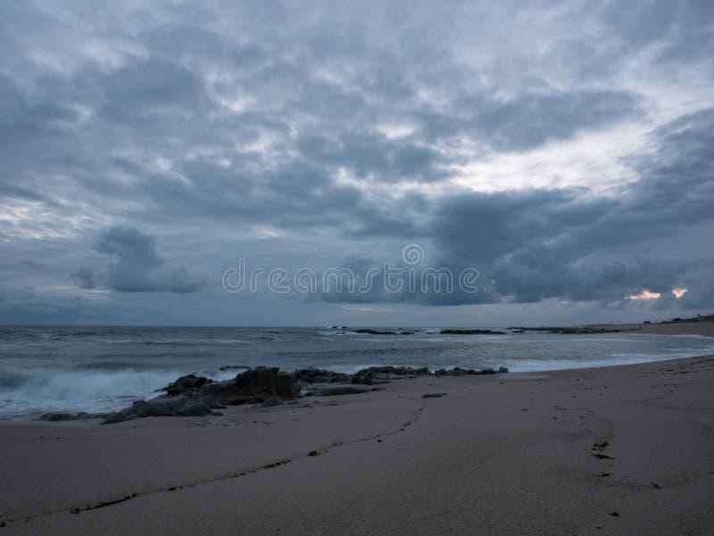 Сумрак на скалистом пляже с темнотой, серым цветом, облачным небом стоковое фото