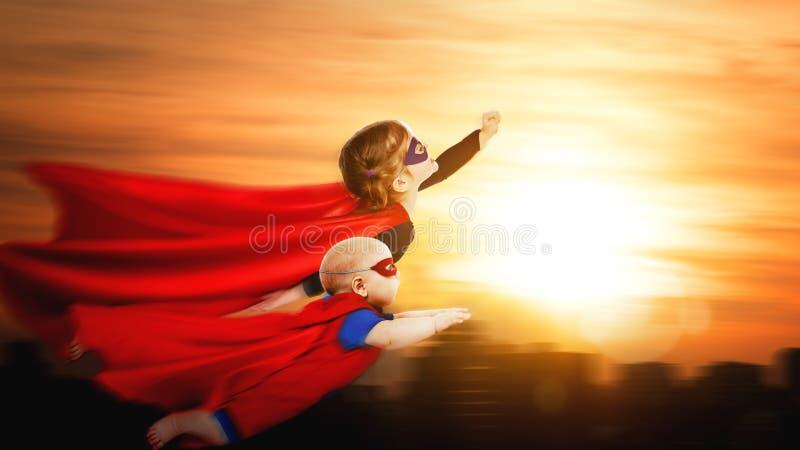 Супергерои детей летая через небо захода солнца стоковое изображение
