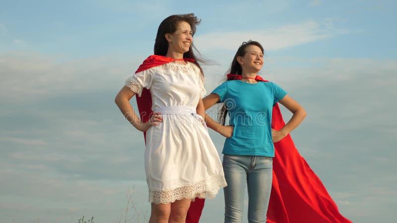 Супергерои игры мамы и дочери 2 девушки в красных плащах супергероев стоят против голубого неба, ветер надувают стоковые изображения rf
