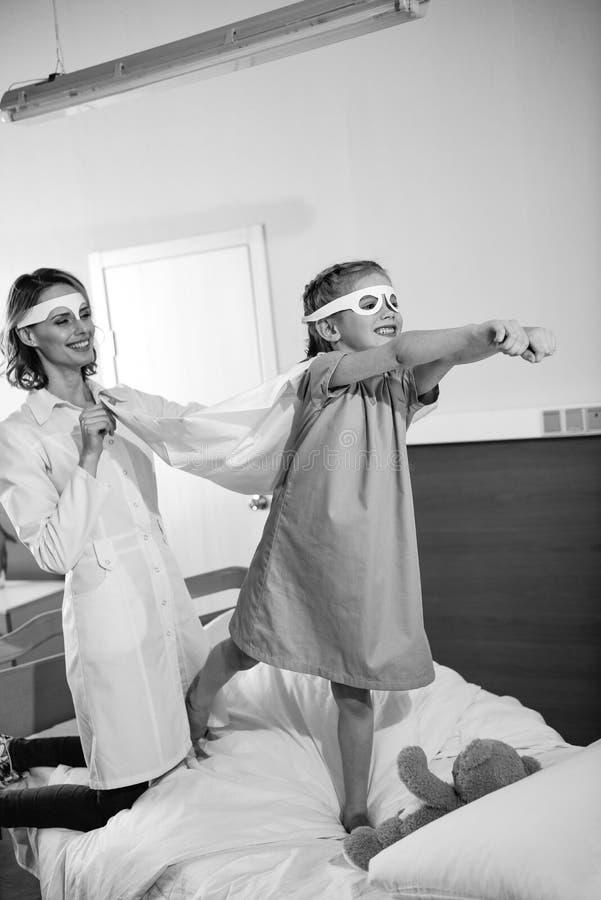 Супергерой маленькой девочки играя с доктором в больнице стоковое изображение