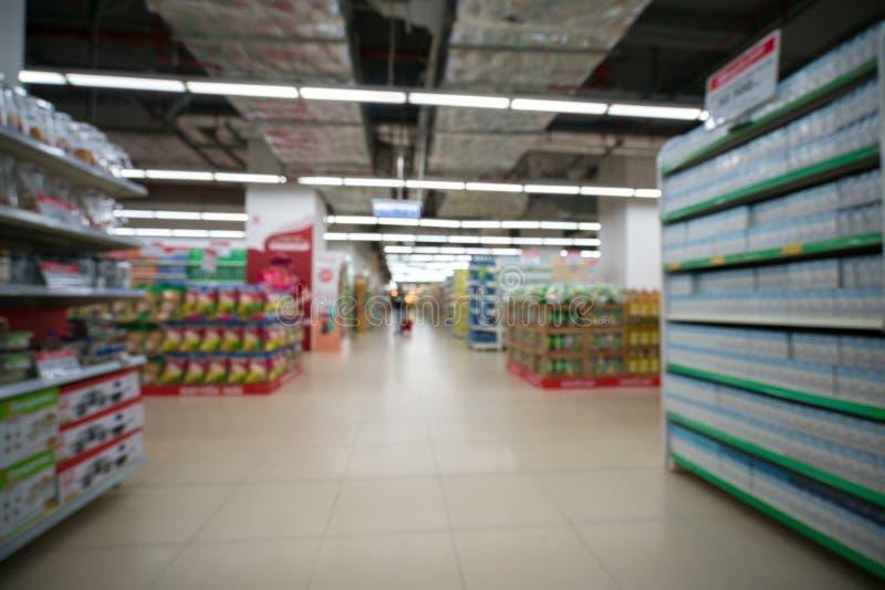 Супермаркет запачкал предпосылку с красочными полками и непознаваемыми клиентами стоковые фото