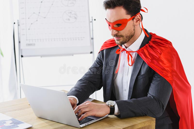 супер бизнесмен в маске и накидка работая с компьтер-книжкой стоковая фотография