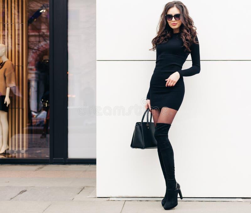 Супер модная длинн-шагающая девушка брюнет с длинными волосами одела в коротком черном платье, пятках черноты высоких с a стоковое фото